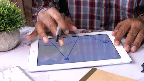 Thumbnail for Businessman Working on Digital Tablet on Office Desk, Using Self Created Chart