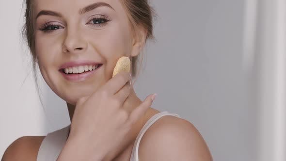 Thumbnail for Close-up of Female Touching Face with Cotton Pad Isolated on Grey