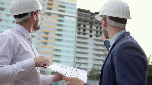 Thumbnail for Two construction engineers discussing a construction plan