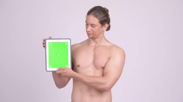 Cover Image for Happy Muscular Shirtless Man Showing Digital Tablet