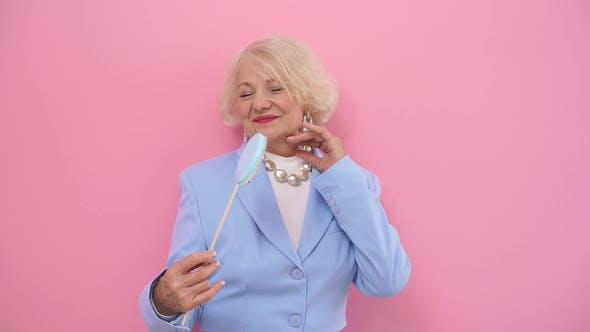 Amazing, Beautiful Mature Woman in a Fashionable Blue Suit Poses for the Camera on a Pink Background