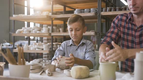 Thumbnail for Caring Father Teaching Little Son How to Work with Clay on Potters Wheel