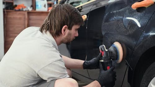 Car Detailing  Hands with Orbital Polisher in Auto Repair Shop