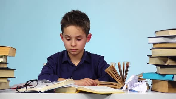Tired Boy Begins To Close and Fold the Book. Blue Background