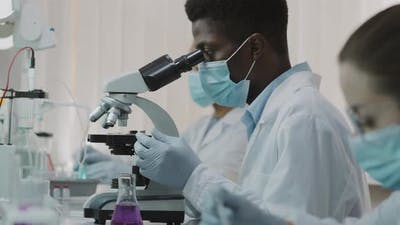 Black Male Scientist in Face Mask Doing Research
