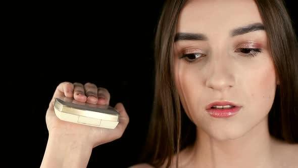 Das Mädchen ist ein Modell eines Make-up-Salons, hält eine Puderbox mit einem Spiegel in der Hand und schließt sie