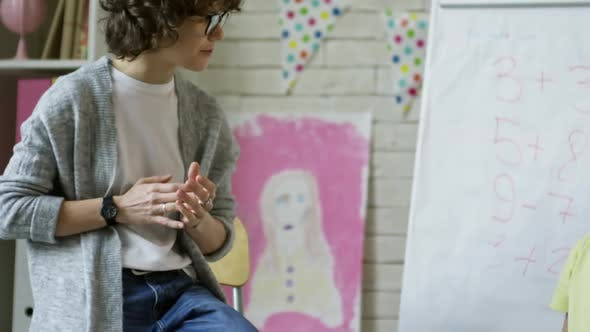 Female Kindergarten Teacher Talking to Little Boy at Lesson
