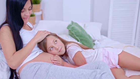 Familienwerte, eine schwangere Mutter liegt mit ihrer Tochter auf dem Bett. Tochter hört auf das Baby in