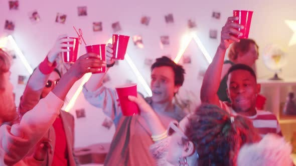 Thumbnail for Young Friends Clicking Cups in a Toast and Dancing at House Party