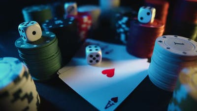 Casino Chips with Dice and Playing Cards on a Dark Table