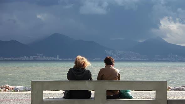 Old Women's Sitting By Beach