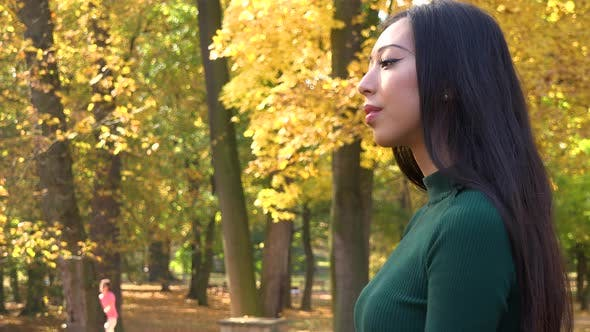 Thumbnail for A Young Asian Woman Looks Around a Park on A Sunny Day