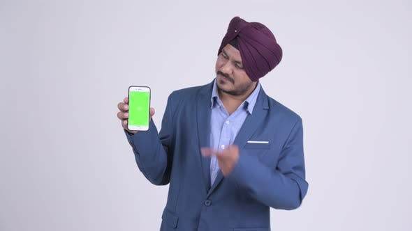 Cover Image for Happy Bearded Indian Sikh Businessman Showing Phone and Giving Thumbs Up