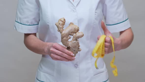 Nutritionist Doctor Healthy Lifestyle Concept - Holding Ginger Root and Measuring Tape