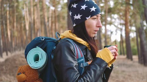 Woman Hiker Having Rest with Hot Drink Tea From Thermos on the Pine Forest