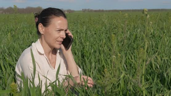 Speak on telephone in the grass.