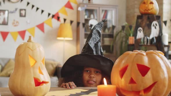 Thumbnail for Little Afro-American Girl in Witch Hat Scaring at Camera
