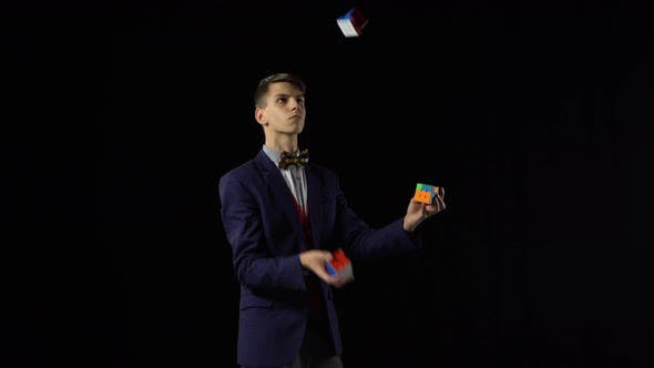 Thumbnail for Handsome Male in Suit Is Juggling Rubik's Cube in Dark.
