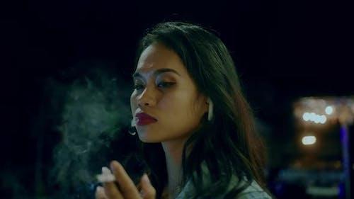 A Girl Smokes Late at Night