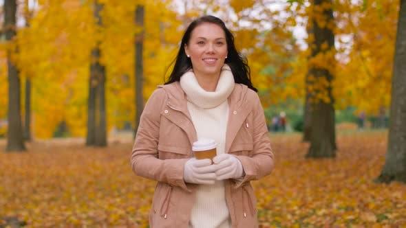 Thumbnail for Frau trinken Kaffee zum Mitnehmen im Herbst Park