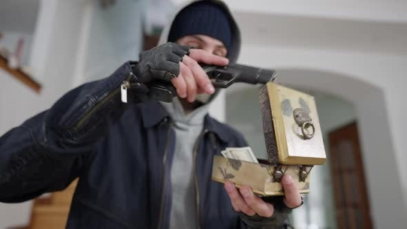 Closeup of Robber Opening Decorative Box with Money Using Weapon