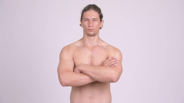 Thumbnail for Handsome Muscular Shirtless Man with Arms Crossed Against White Background