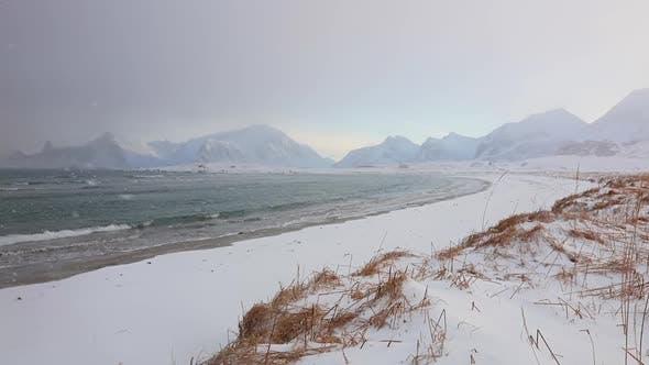 Snowfall on the Winter Beach on the Sea Coast Between Mountains