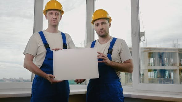 Thumbnail for Two sad builders with boardsheet or poster looking for a job.