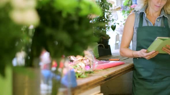 Thumbnail for A Florist stands in her shop using her digital tablet