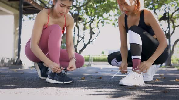 Young Asian Female Runners in Park Tying Shoe Lace