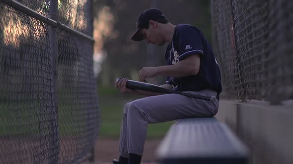 Thumbnail for A baseball player resting on the bench.