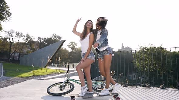 Two Cuddy Jovial Sexy Girls in Fashion Clothes Standing by One Leg on Skateboard with Raised Hands