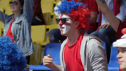 Devoted Caucasian Fan with Painted Face Rejoicing at Goal