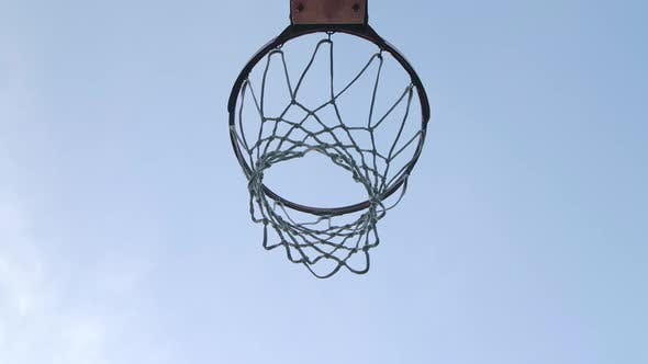 Basketball Balls Falls Through the Hoop Towards the Camera and Hits the Ring. Bottom View. Close Up
