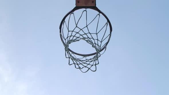 Basketball Balls Falls Through the Hoop Towards the Camera and Hits the Ring. Bottom View. Close Up