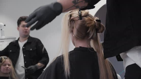 Hairdresser In Hair Salon Chatting To Customer
