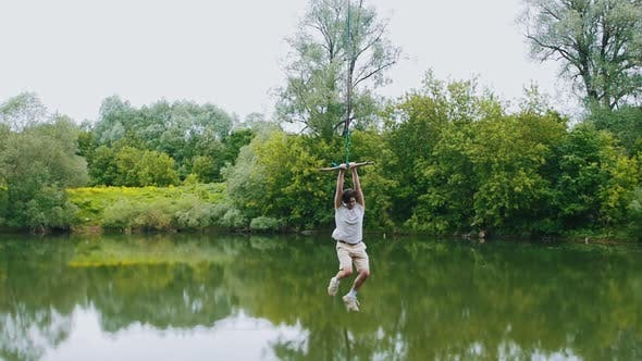 Thumbnail for Young Man Flying Above the Water Holding By the Bar