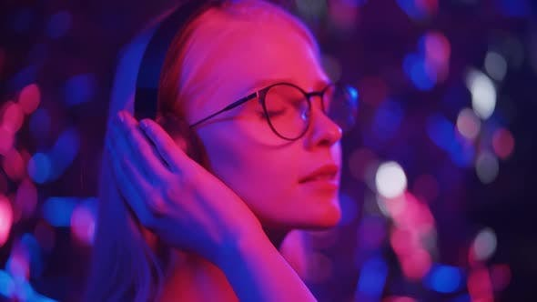 Happy Young Blonde Woman in Glasses Dances in Headphones on a Background of Multicolored Lights