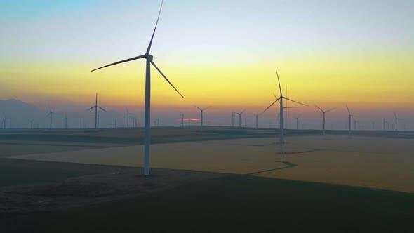 Eolische Turbinenfarm bei Sonnenaufgang. Silhouette von Windturbinen Windfeldturbinen