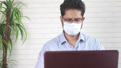 Businessman in Face Mask Working on Laptop