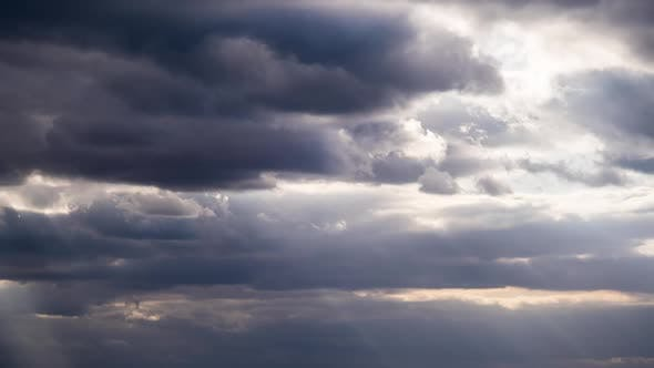 Thumbnail for Sunbeams Shine Behind the Amazing Dramatic Storm Clouds in the Sky. Time Lapse