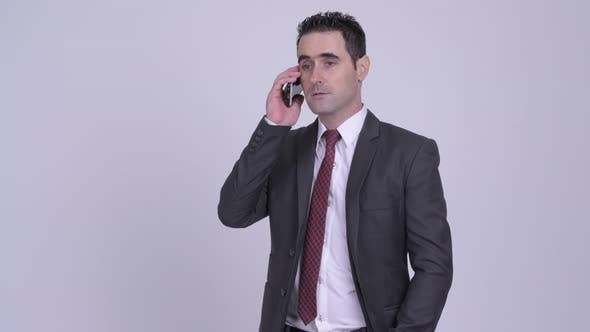 Thumbnail for Happy Handsome Businessman Thinking While Talking on the Phone