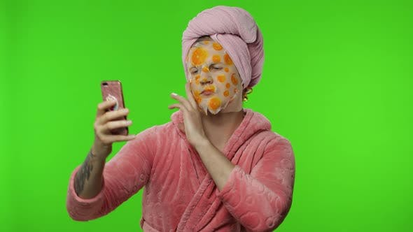 Thumbnail for Transsexual Man in Bathrobe with Face Mask Making Selfies Using Mobile Phone