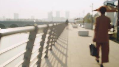 People Walking on Embankment in City