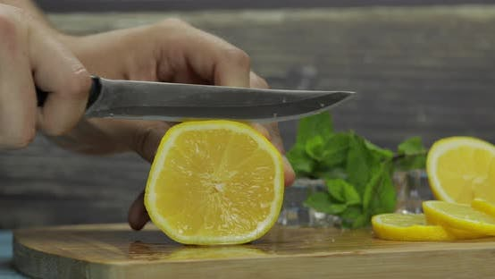 Thumbnail for Man Slicing Lemon on a Wooden Cutting Board in the Kitchen