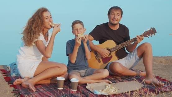 Thumbnail for Familie aktiv kommunizieren während Picknick auf einem Hügel und Snack mit Kaffee und Pizza