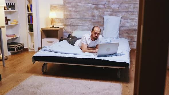 Freelancer Wearing Pajamas Working on Laptop