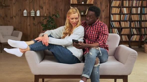 Vielfältiges verliebtes Paar verbringt Freizeit online mit einem Smartphone