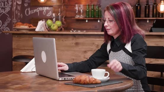 Woman Drinks Coffee While Typing on Laptop Keyboard