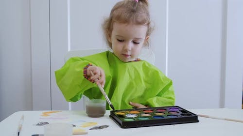 A Young Artist of Two or Three Years Draws Color Circles in Watercolor on White Paper.